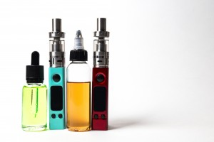 e- liquid, e-juice in the bottles and e-cigarette (vape)  isolated on the white background with copyspace